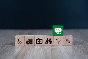 Wooden toy blocks stacked with medical icon for medical and health insurance concepts.